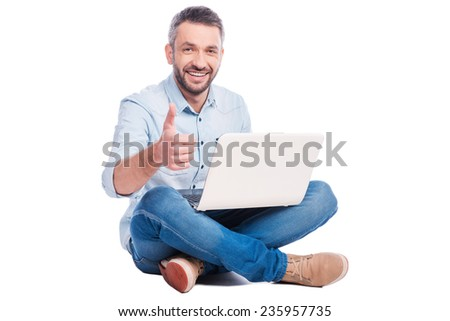 Technologies become easier! Handsome young man in casual wear sitting on the floor with laptop and showing his thumb up while being isolated on white background - stock photo