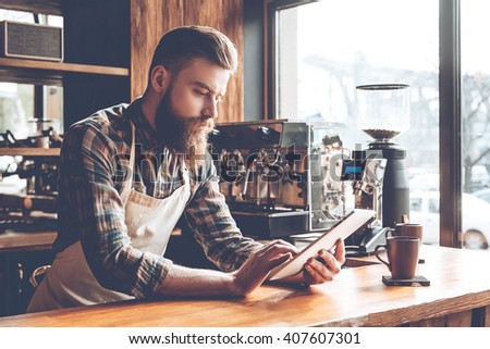 Technologies make business easier. Young bearded man in apron using his digital tablet while leaning to bar counter at cafe - stock photo