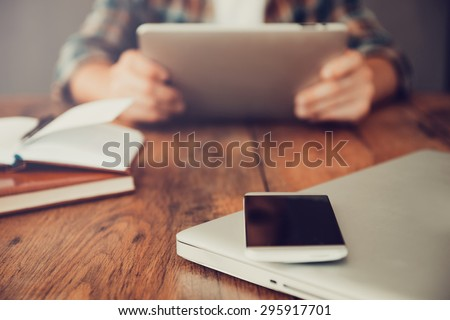 Technologies make life easier. Close-up of man holding digital tablet while mobile phone and laptop laying on foreground  - stock photo
