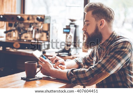 Technologies make life easier. Side view of young handsome man using his digital tablet while sitting at bar counter at cafe  - stock photo
