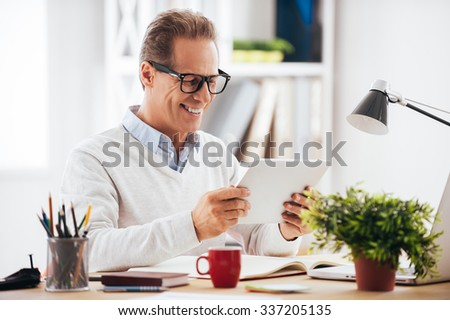 Technologies making life easier. Cheerful mature man holding digital tablet and looking at it with smile while sitting at his working place - stock photo