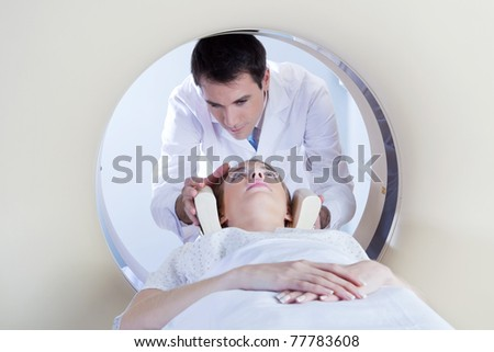 Technologist preparing the patient for a CT scan in hospital - stock photo
