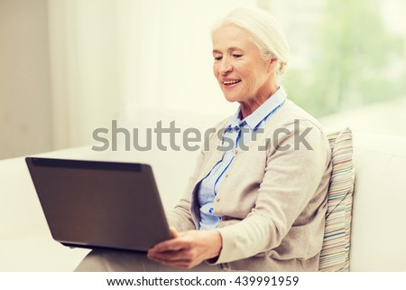 technology, age and people concept - happy senior woman with laptop computer at home - stock photo