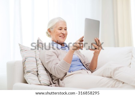 technology, age and people concept - happy senior woman with tablet pc computer at home - stock photo