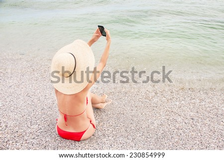 Technology and beach concept. Caucasian resting woman on vacation is sitting on the beach with sea and making self portrait by smart phone (mobile). Relaxing female model in red bikini. Copy space. - stock photo