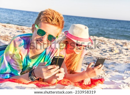 Technology and beach concept. Teenagers (boy and girl) using smart phone (mobile) and listening music with headphone on the beach. Happy teens are wearing colorful sunglasses. Summer holidays.  - stock photo