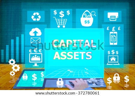 technology and biz concept. working on his laptop in the secured office, select  icon  capital assets on the virtual display - stock photo