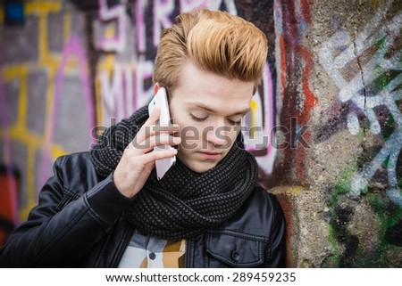 Technology and communication. Closeup young fashion man talking on mobile cell phone using smartphone outdoor graffiti wall background