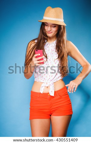 Technology and internet. Happy woman using cellphone texting on mobile phone. Teen girl reading sms on smartphone, taking selfie on blue - stock photo