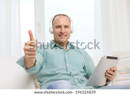 technology and lifestyle, distance learning concept - handsome man with tablet pc computer and headphones at home showing thumbs up - stock photo