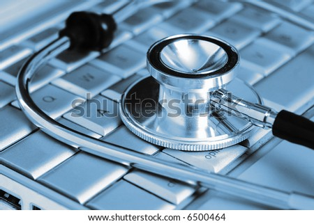 Technology and medicine - Silver stethoscope over laptop keyboard - stock photo