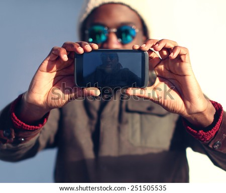 Technology and people concept - modern stylish african man makes selfie, screen front view  - stock photo
