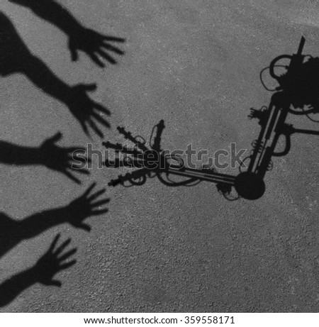 Technology and society concept as a shadow of reaching people hands interacting greeting an advanced computer aided robot arm as a work assistant symbol and artificial intelligence social issue. - stock photo