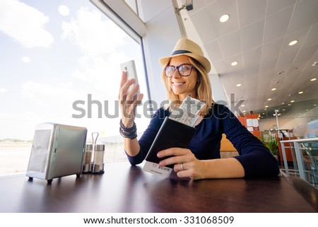 Technology and traveling. Pretty young woman in hat using smarthone while waiting for boarding in the airport. - stock photo