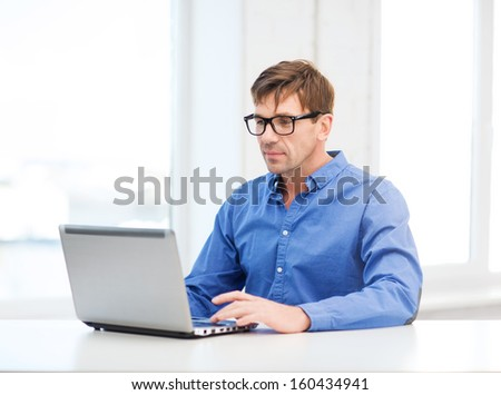 technology, business and lifestyle concept - man in eyeglasses working with laptop at home