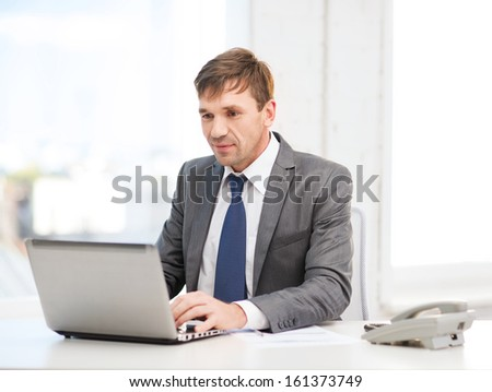 technology, business and office concept - handsome businessman working with laptop computer and documents - stock photo