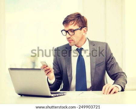 technology, business and office concept - handsome businessman working with laptop computer and smartphone - stock photo