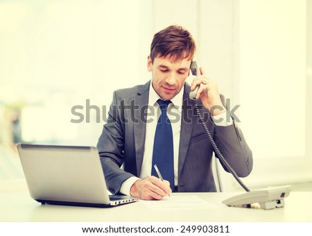 technology, business and office concept - handsome businessman working with laptop computer, phone and documents - stock photo