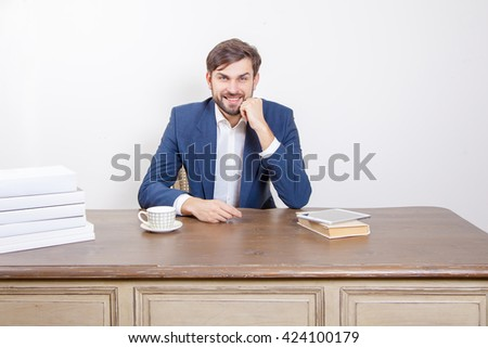 Technology, Business concept - handsome man with beard and brown hair and blue suit and tablet pc computer and some books looking at camera with smile in the office.  Isolated on white background.   - stock photo