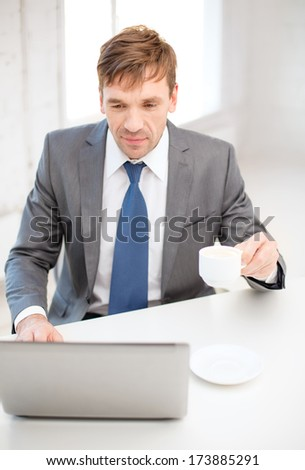 technology, business, internet and office concept - handsome businessman working with laptop computer