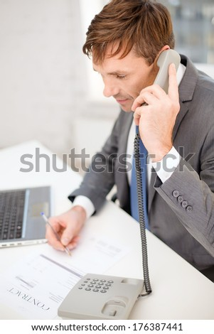 technology, business, internet and office concept - handsome businessman working with laptop computer, phone and documents - stock photo