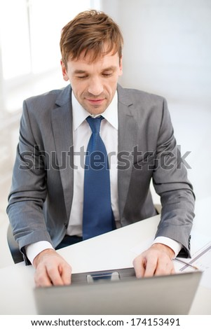 technology, business, internet and office concept - puzzled businessman working with laptop computer and documents
