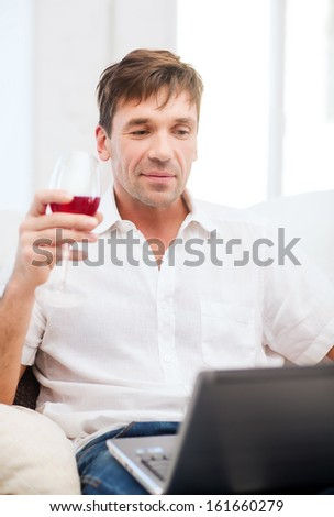 technology, business, leisure, drinks, retirement and lifestyle concept - happy man with laptop computer and glass of rose wine at home - stock photo