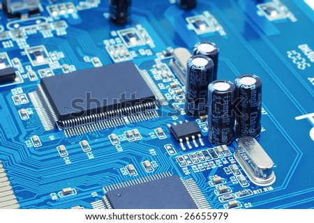 Technology: capacitors and chips on blue microcircuit board - stock photo