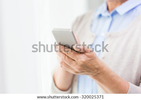 technology, communication age and people concept - close up of senior woman hands with smartphone texting message at home - stock photo