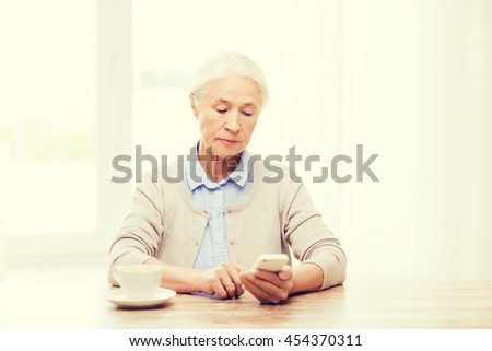 technology, communication age and people concept - senior woman with smartphone and coffee sitting at table and texting message at home