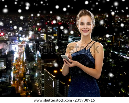technology, communication and people concept - smiling woman in evening dress holding smartphone over snowy night city background - stock photo