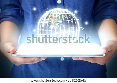 technology communication concept.  Hand women holding Globe from tablet pc. Touch pad interface.Elements of this image furnished by NASA