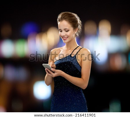 technology, communication, holidays and people concept - smiling woman in evening dress holding smartphone over night lights background - stock photo