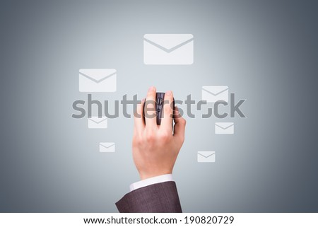 Technology concept, businessman hand holding mouse with mail symbols on dark background. - stock photo