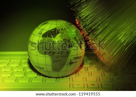 technology earth on laptop keyboard against fiber optic background