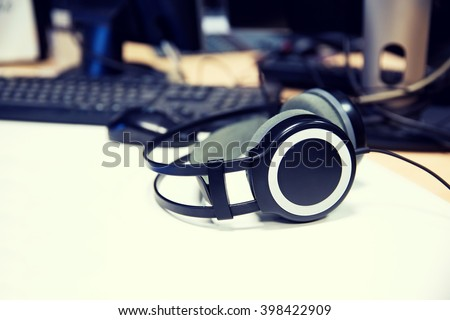 technology, electronics and audio equipment concept - close up of headphones at recording studio or radio station - stock photo