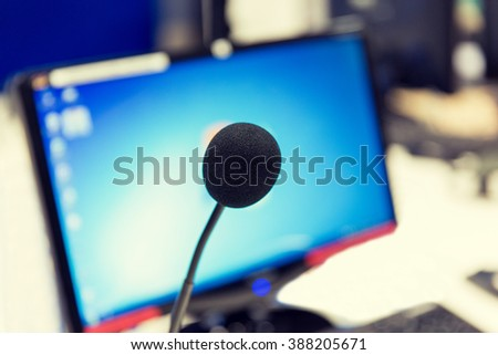 technology, electronics and audio equipment concept - close up of microphone and computer monitor at recording studio or radio station - stock photo