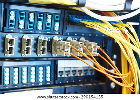 technology equipment with optical fibre cables connected to rack servers in room. Shallow DOF - stock photo