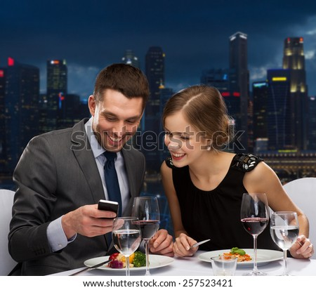 technology, food, holidays and people concept - smiling couple with smartphone eating at restaurant over night city background