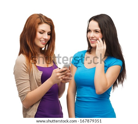 technology, friendship and leirure concept - two smiling teenagers with smartphones texting and calling - stock photo