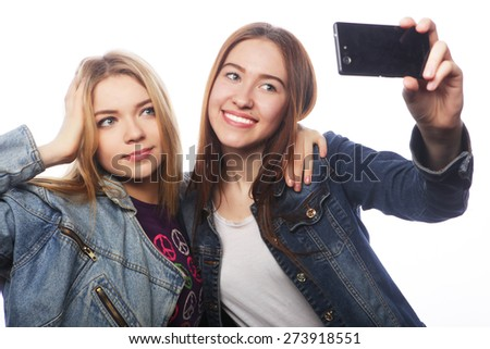 technology, friendship and people concept - two smiling teenagers taking picture with smartphone camera - stock photo