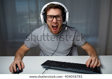 technology, gaming, entertainment, let's play and people concept - angry screaming young man in headset with pc computer playing game at home and streaming playthrough or walkthrough video - stock photo