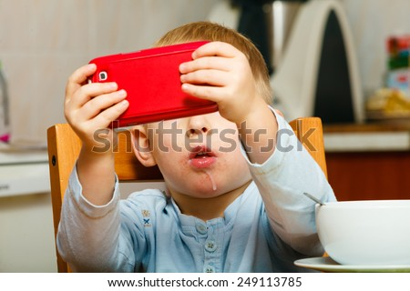 Technology generation. Happy childhood. Little boy child dirty mouth drooling, eating breakfast playing with mobile phone at table. Home. - stock photo