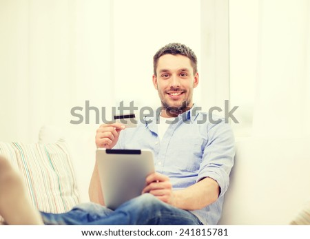technology, home and lifestyle concept - smiling man working with tablet pc computer and credit card at home - stock photo