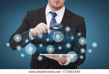 technology, internet and business concept - businessman holding magnifying glass over tablet pc computer - stock photo