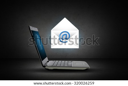 technology, internet and communication concept - open laptop computer with e-mail icon and virtual letter over dark gray background - stock photo