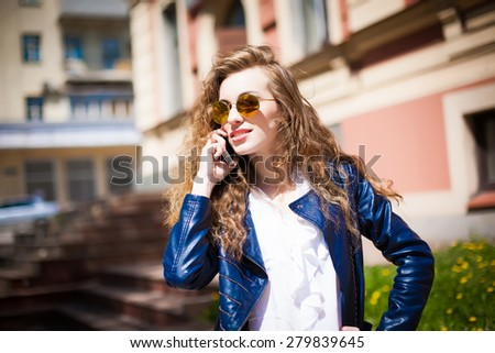 Technology internet and happy people concept - beautiful succesfull woman in sunglasses talking on cellphone while walking outdoor. City business woman working. Stylish purse. - stock photo