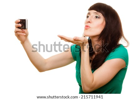 Technology internet, love relationship and dating concept - smiling woman taking self picture with smartphone camera blowing kiss isolated - stock photo