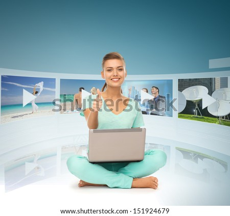 technology, internet, tv and news concept - young woman with laptop pc and virtual screens - stock photo