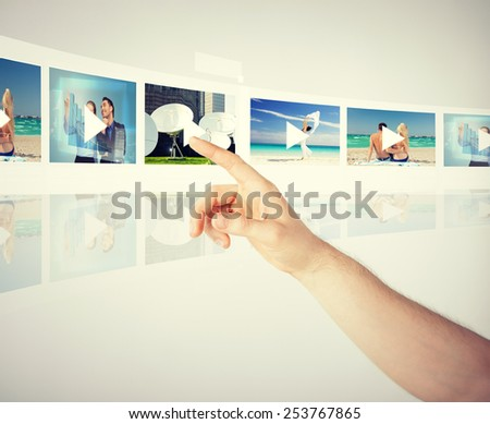 technology, internet, tv and virtual screens concept - man pressing button on virtual screen with videos - stock photo